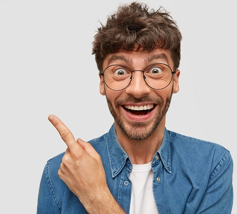 Joyful European male with broad smile, has funny expression, indicates aside, advertises something amazing, dressed casually, isolated over white background with copy space for promotional text