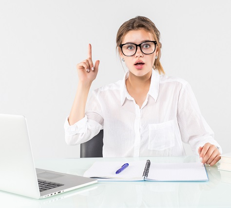 Young excited woman in pastel clothes holding index finger up with great new idea sit, work at desk with laptop isolated on gray background.